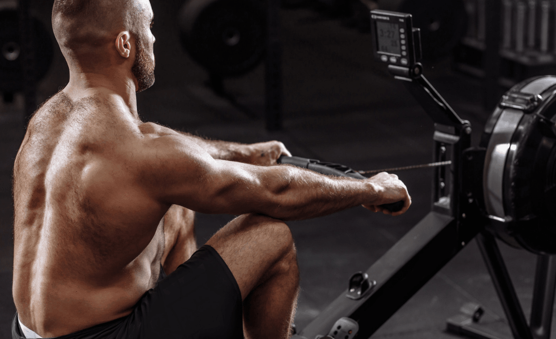 shirtless man using inexpensive rowing machine